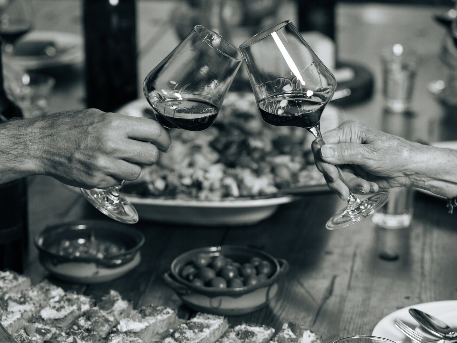 Hands holding wine glasses toasting